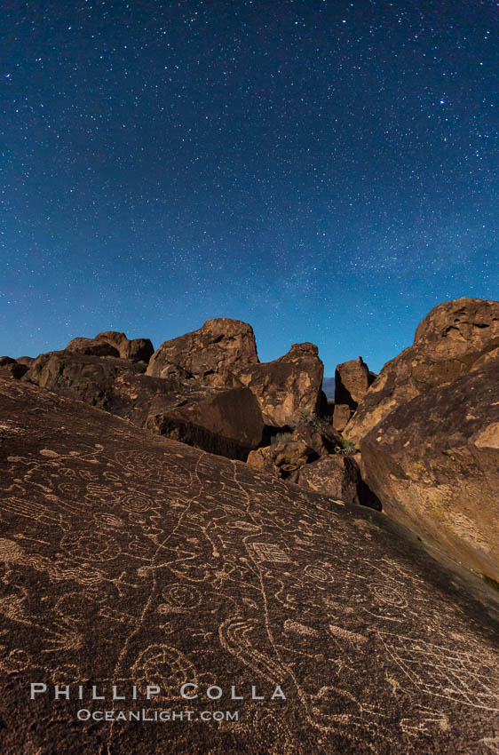 Sky Rock at night, light by moonlight with stars in the clear night sky above.  Sky Rock petroglyphs near Bishop, California. Hidden atop an enormous boulder in the Volcanic Tablelands lies Sky Rock, a set of petroglyphs that face the sky. These superb examples of native American petroglyph artwork are thought to be Paiute in origin, but little is known about them., natural history stock photograph, photo id 28499