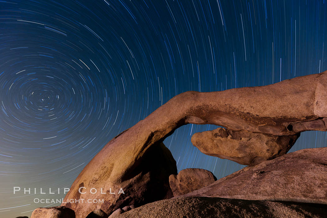 Star trails and Arch Rock.  Polaris, the North Star, is at the center of the circular arc star trails as they pass above this natural stone archway in Joshua Tree National Park. California, USA, natural history stock photograph, photo id 26794