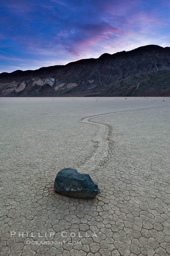 Sunrise on the Racetrack Playa. The sliding rocks, or sailing stones, move across the mud flats of the Racetrack Playa, leaving trails behind in the mud. The explanation for their movement is not known with certainty, but many believe wind pushes the rocks over wet and perhaps icy mud in winter. Racetrack Playa, Death Valley National Park, California, USA, natural history stock photograph, photo id 27699