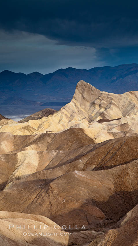 Sunrise at Zabriskie Point, Manly Beacon is lit by the morning sun while dark clouds lie on the horizon. Death Valley National Park, California, USA, natural history stock photograph, photo id 25256