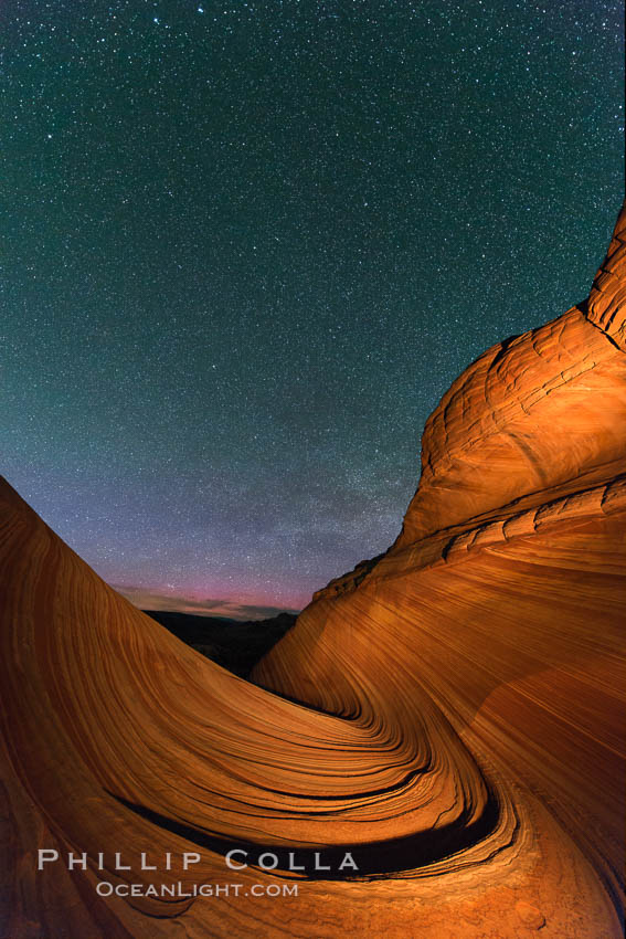 Image 28623, The Wave at Night, under a clear night sky full of stars.  The Wave, an area of fantastic eroded sandstone featuring beautiful swirls, wild colors, countless striations, and bizarre shapes set amidst the dramatic surrounding North Coyote Buttes of Arizona and Utah. The sandstone formations of the North Coyote Buttes, including the Wave, date from the Jurassic period. Managed by the Bureau of Land Management, the Wave is located in the Paria Canyon-Vermilion Cliffs Wilderness and is accessible on foot by permit only. North Coyote Buttes, Paria Canyon-Vermilion Cliffs Wilderness, Arizona, USA, Phillip Colla, all rights reserved worldwide. Keywords: arizona, astrophotography, astrophotography landscape, barren, butte, cliffs, desert, diagenic coloration, dusk, environment, erosion, evening, geology, landmark, landscape, landscape astrophotography, layers, national parks, nature, night, nightscape, north coyote buttes, outdoors, outside, paria, paria canyon vermilion cliffs wilderness, paria canyon-vermilion cliffs wilderness, rock, sandstone, scene, scenic, sedimentary, sedimentary rock, stars, stratigraphic relationship, the wave, usa, vermilion, vermilion cliffs national monument, vermillion, wave coyote buttes, wilderness.