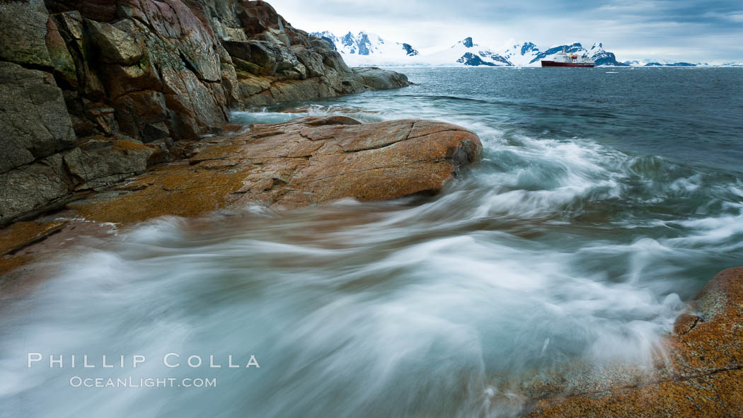 Waves rush in, sunset, Antarctica.  Ocean water rushes ashore over the rocky edge of Peterman Island, Antarctica. Peterman Island, Antarctic Peninsula, Antarctica, natural history stock photograph, photo id 25620