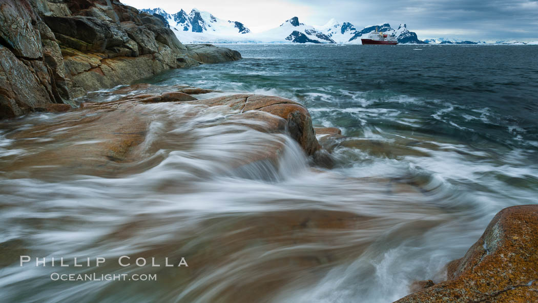 Waves rush in, sunset, Antarctica.  Ocean water rushes ashore over the rocky edge of Peterman Island, Antarctica. Peterman Island, Antarctic Peninsula, Antarctica, natural history stock photograph, photo id 25636