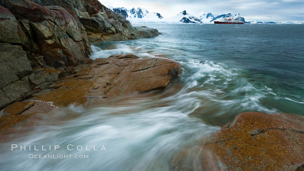 Waves rush in, sunset, Antarctica.  Ocean water rushes ashore over the rocky edge of Peterman Island, Antarctica. Peterman Island, Antarctic Peninsula, Antarctica, natural history stock photograph, photo id 25637
