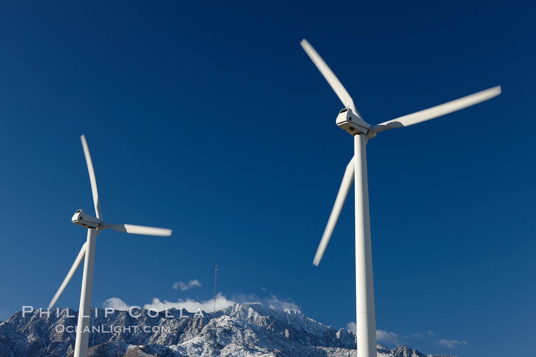 Wind turbines, rise above the flat floor of the San Gorgonio Pass near Palm Springs, with snow covered Mount San Jacinto in the background, provide electricity to Palm Springs and the Coachella Valley. California, USA, natural history stock photograph, photo id 22206
