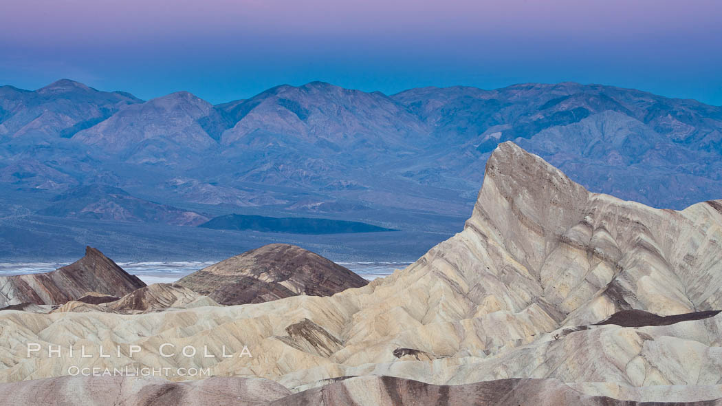 Zabriskie Point, sunrise.  Manly Beacon rises in the center of an eroded, curiously banded area of sedimentary rock, with the Panamint Mountains visible in the distance. Death Valley National Park, California, USA, natural history stock photograph, photo id 15585