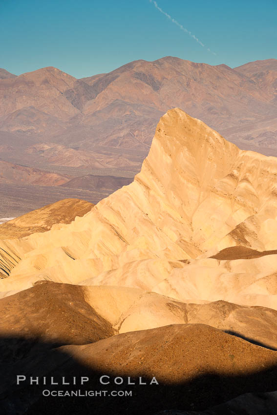 Zabriskie Point, sunrise.  Manly Beacon rises in the center of an eroded, curiously banded area of sedimentary rock, with the Panamint Mountains visible in the distance. Zabriskie Point, Death Valley National Park, California, USA, natural history stock photograph, photo id 15586
