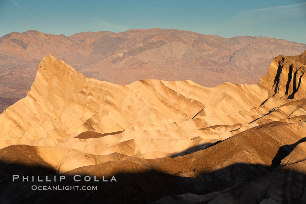 Zabriskie Point, sunrise.  Manly Beacon rises in the center of an eroded, curiously banded area of sedimentary rock, with the Panamint Mountains visible in the distance. Death Valley National Park, California, USA, natural history stock photograph, photo id 15619